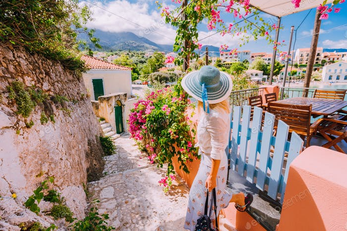 Young female on summer vacation in Greece looking towards wonderful summer day. Cute woman leaving