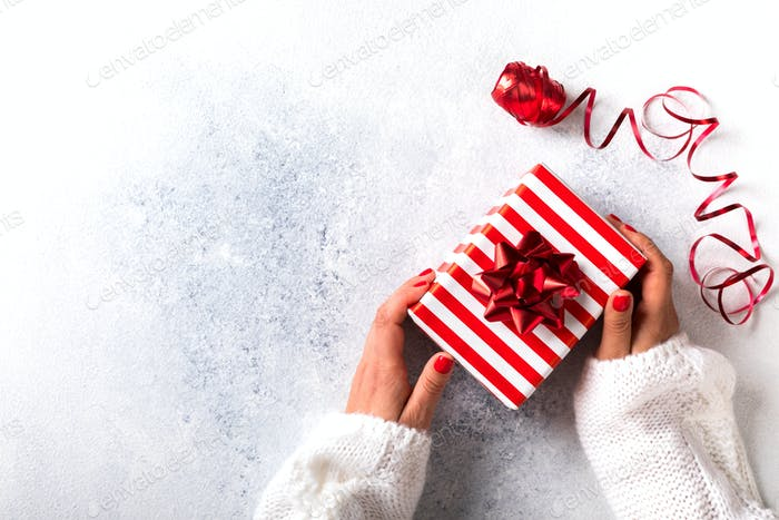 Christmas Gift Box in female hands.Tradition Decoration Holiday