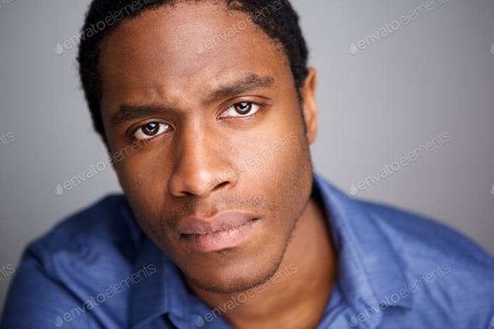 Close up serious young african american man against gray background