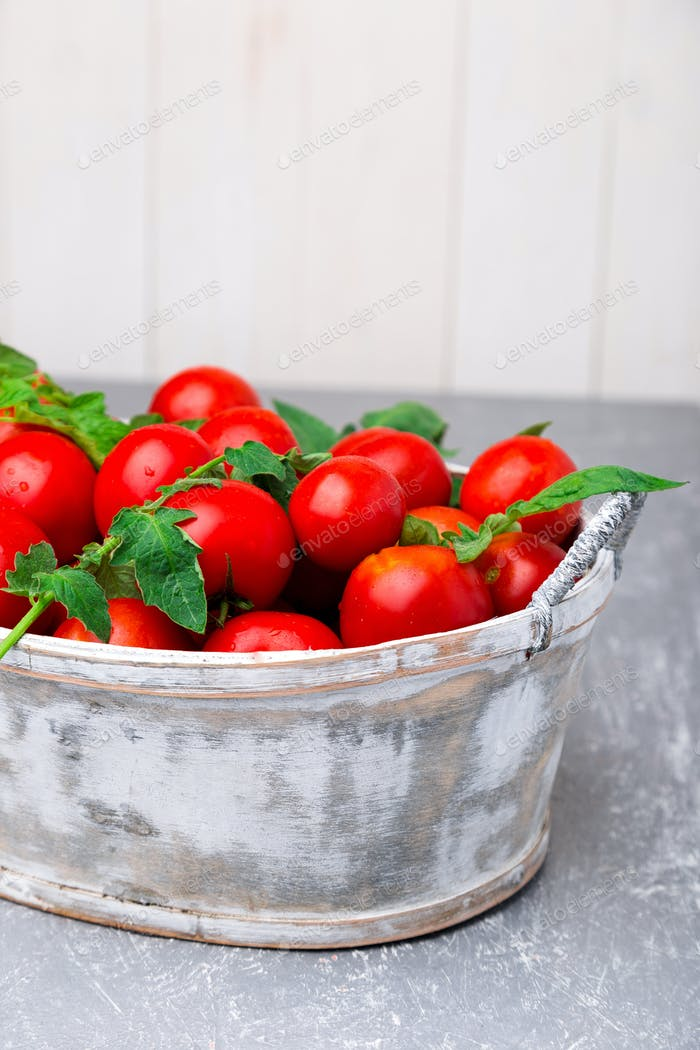Red tomato in grey basket on grey background. Harvest.  Full box of tomatoes.