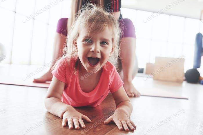 Симпатичная счастливая молодая девушка смотрит прямо в камеру и улыбается с мамой, сидящей позади