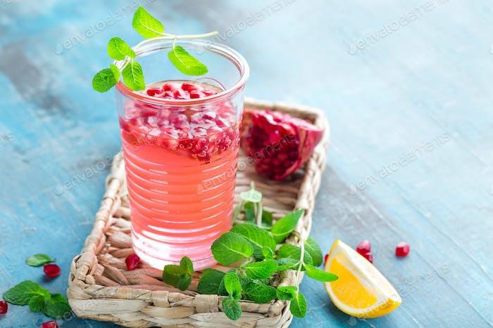 Infundiertes Granatapfelwasser mit frischer Zitrone und Eis, kalte gesunde erfrischende und Entgiftungsgetränk