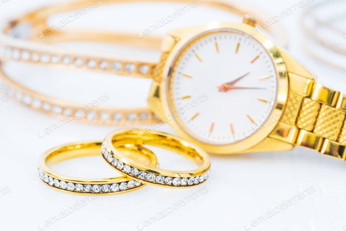 Luxury gold ring and lady gold watch on white_