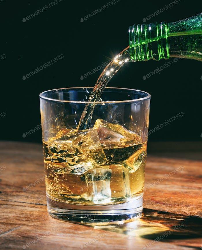 Grüne Flasche Gießen Whisky in Kristallglas mit Eiswürfeln auf Holztisch.