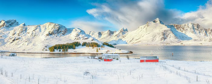 Panoramic winter view on Selfjorden with small fishing houses (rorbu) and snowy peaks on background