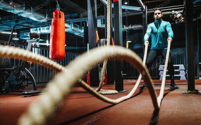 Фитнес-человек тренируется с боевыми веревками в тренажерном зале