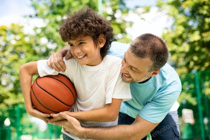 Joyful dad playing basketball with his son outdoors