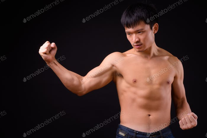 Portrait of young muscular Asian man shirtless ready to fight
