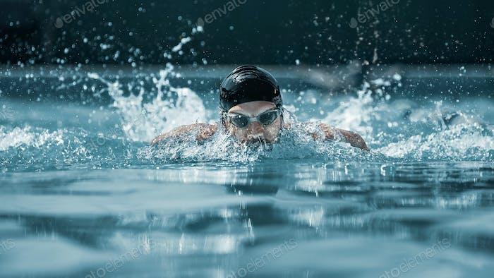 nadador dinámico y en forma en la respiración de la tapa realizando el golpe de mariposa