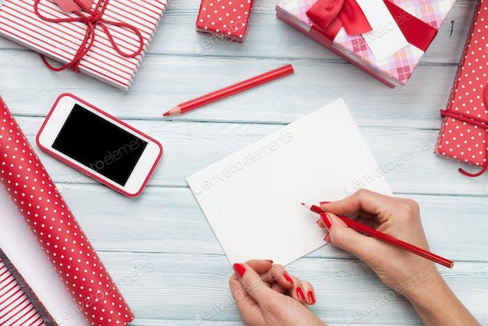 Female writing xmas greeting card