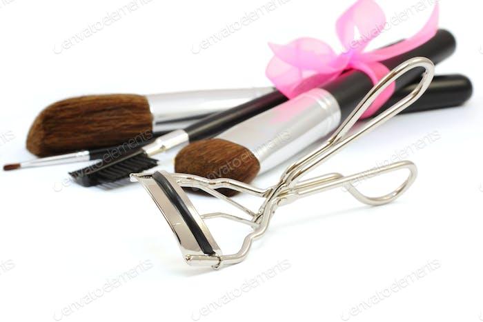 Eyelash curler and make-up brushes isolated on white