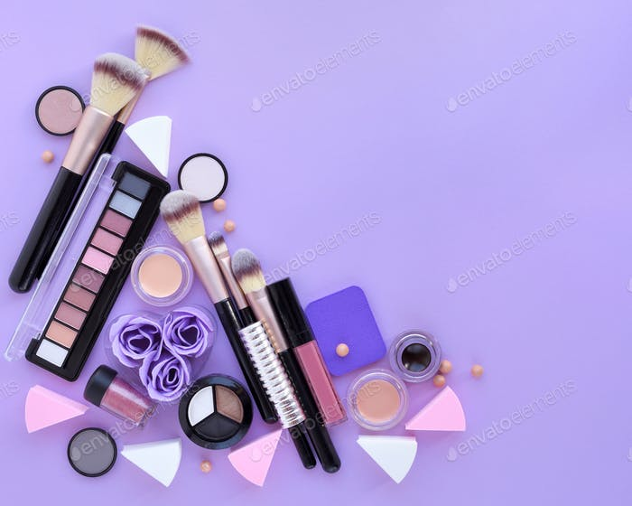 Makeup brush and decorative cosmetics on lilac background. Top v