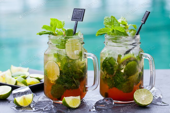 Mojito Cocktail in Glass Jars on Blue Water Background. Copy Space.