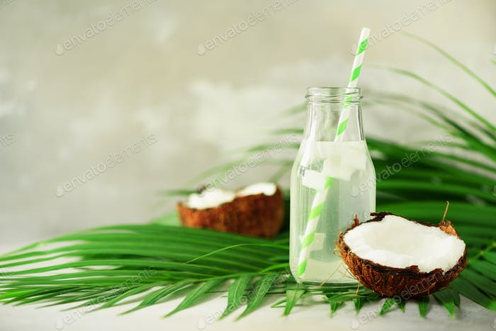 Bottle of coconut water and fresh ripe fruits on grey concrete background. Summer food concept