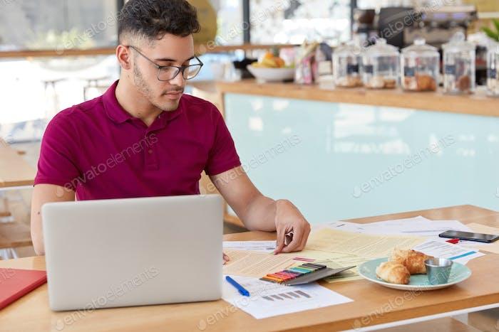 Disparo de joven macho utiliza computadora portátil para comprobar el tipo de cambio en internet, trabaja con financieros