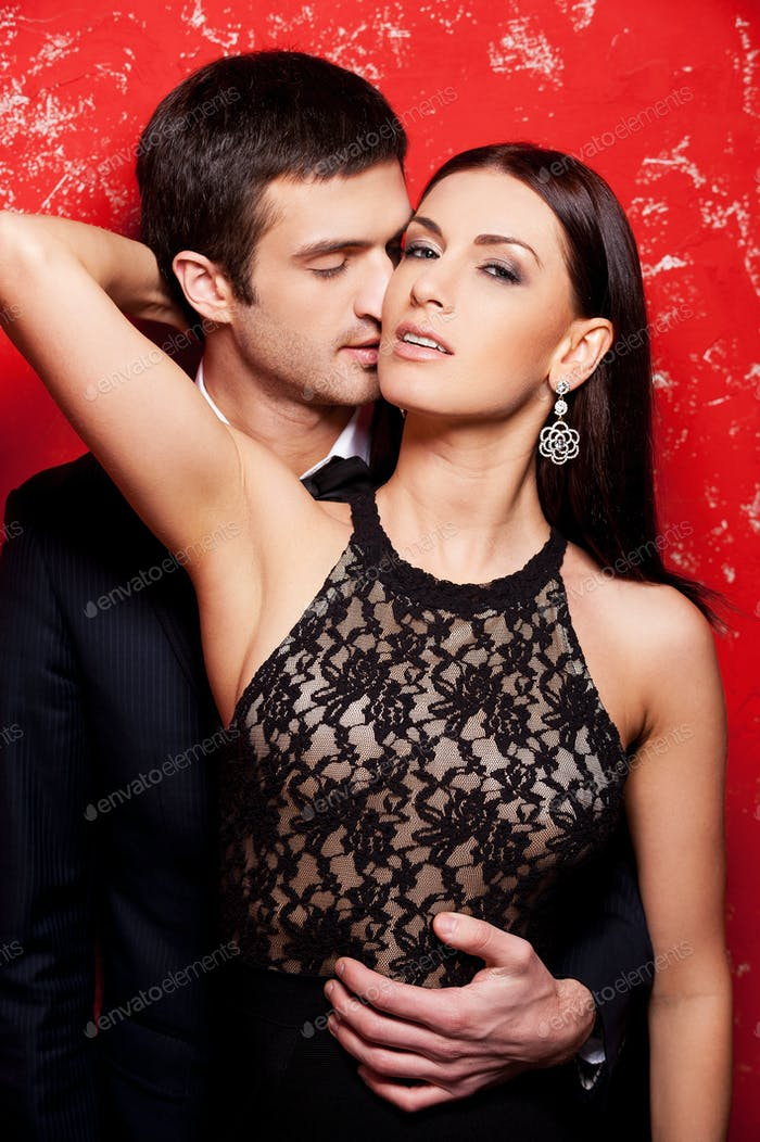 Elegant couple on red. Beautiful young well-dressed couple posing against red background