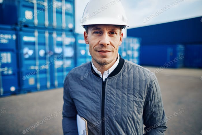 Smiling engineer standing alone on a commercial shipping dock
