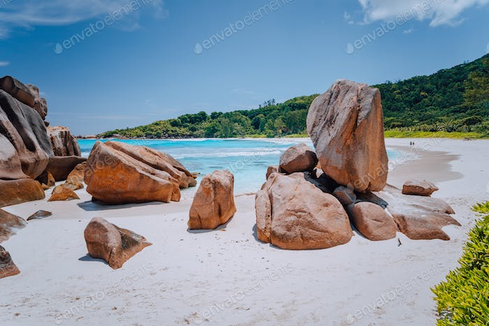 Couple on tropical beach lagoon with granite boulders in the turquoise water and a pristine white
