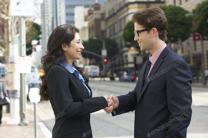 Geschäftsmann und Geschäftsfrau schütteln Hände in Straße