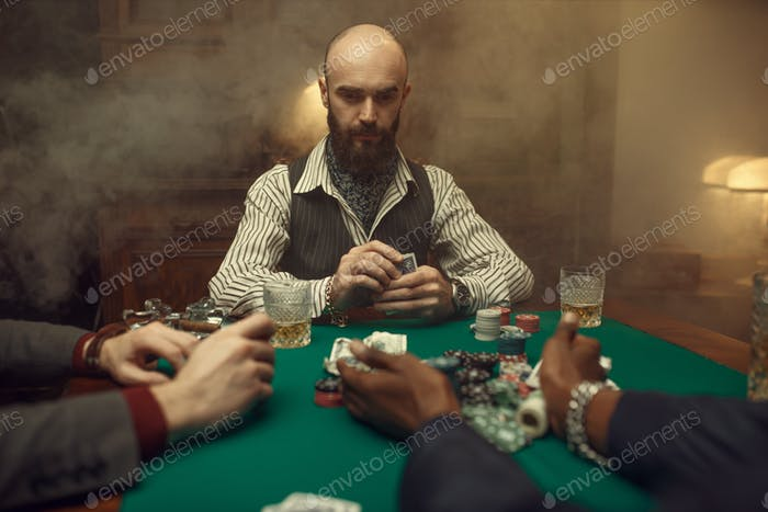 Poker players with cards and chips in casino