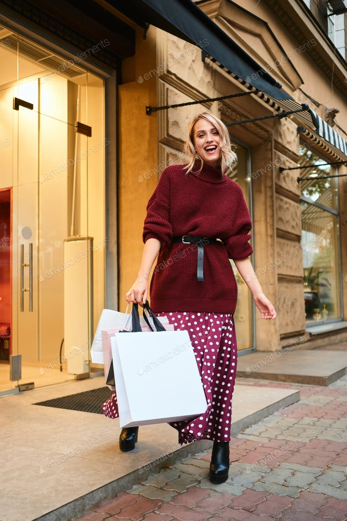 Attractive joyful blond girl in knitted sweater with shopping bags happily shopping outdoor
