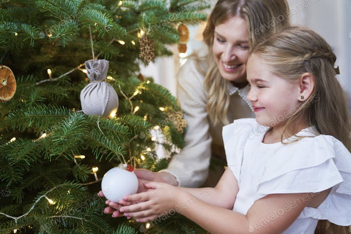 Cute girl decorating the Christmas tree with mum