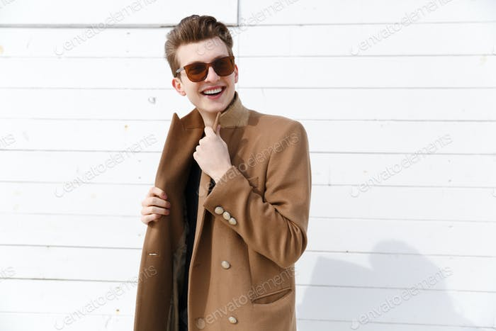 Portrait of smiling attractive young man in coat and sunglasses