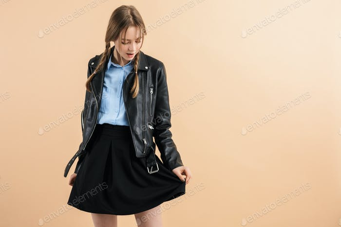 Young dreamy school girl with braids in leather jacket and skirt thoughtfully looking aside