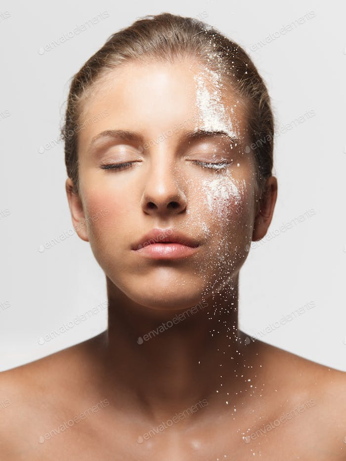 young woman loose powder on her face