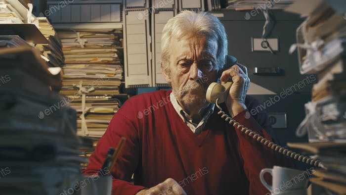 Senior businessman answering phone calls in the office