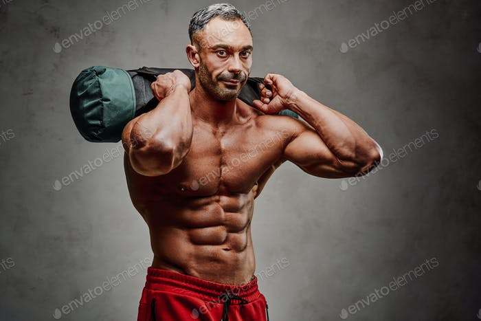 Healthy and energetic man doing lifting exercises, focused and looking strong
