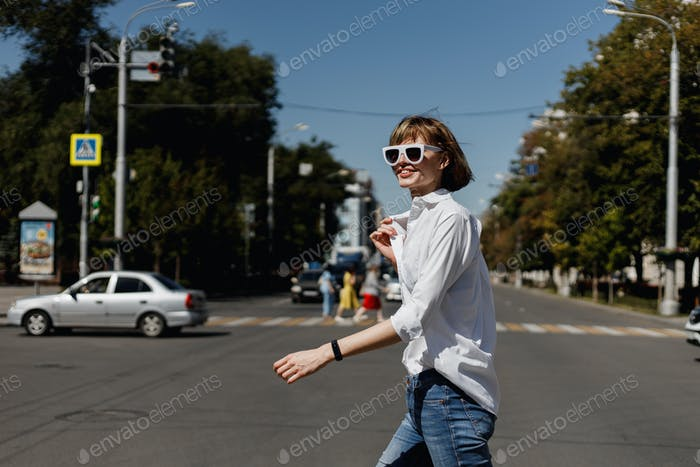 Stylish young woman in white sunglasses dressed in white shirt and jeans is crossing in a city on a