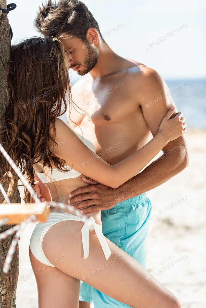 beautiful couple embracing on beach in summer