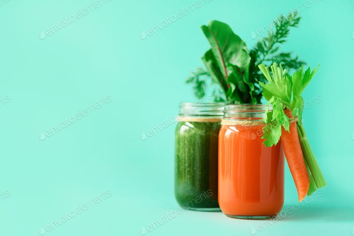 Healthy organic green and orange smoothies on blue background. Detox drinks in glass jar from