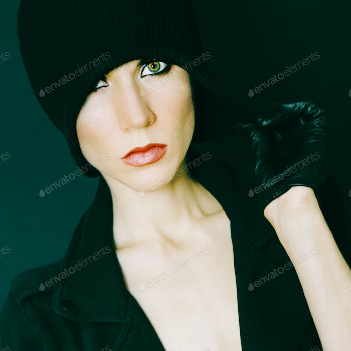 glamorous lady on black background in trendy gloves and hat autu