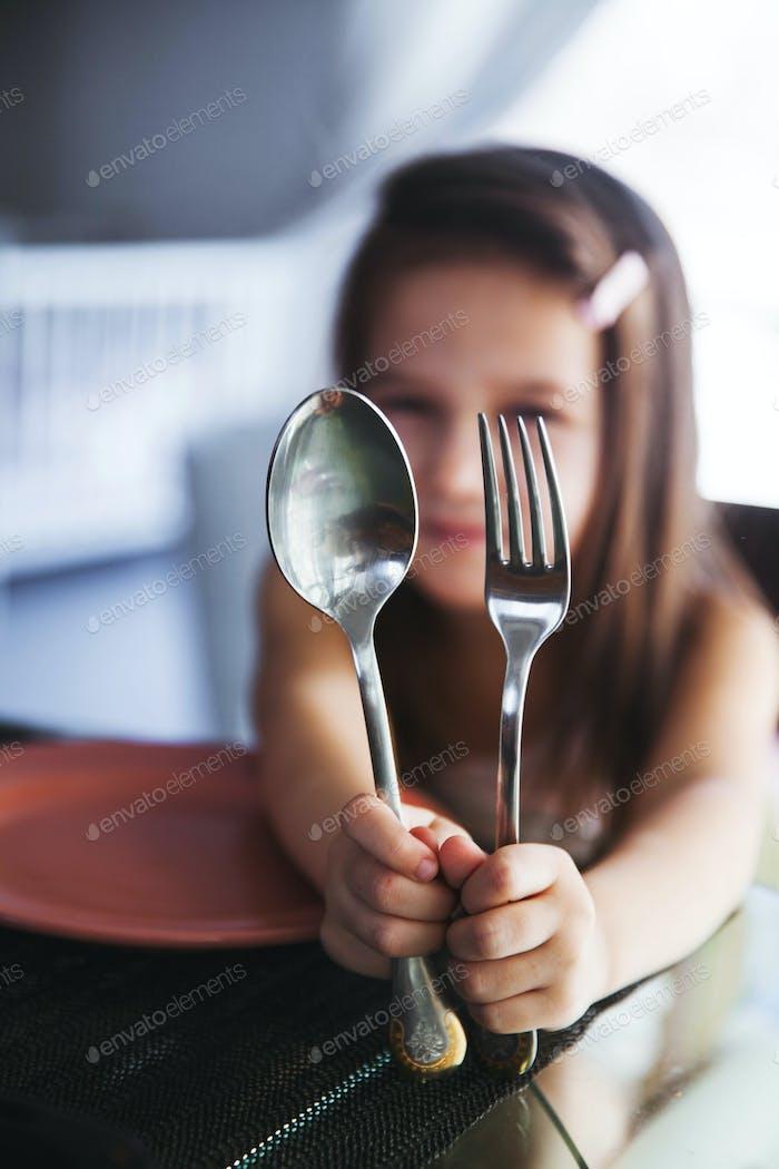 Hermosa chica sosteniendo una cuchara y tenedor