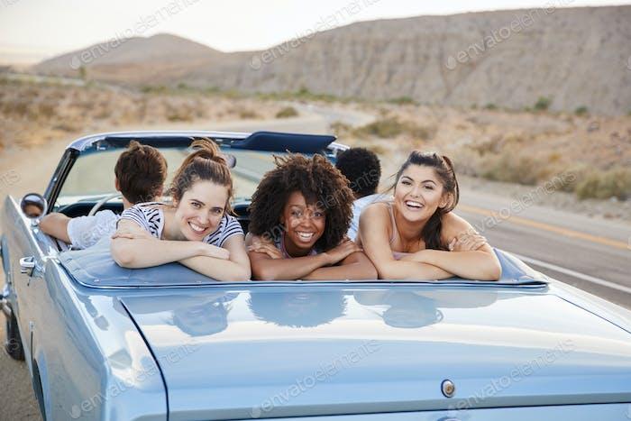 Portrait Of Three Female Friends Enjoying Road Trip In Open Top Classic Car