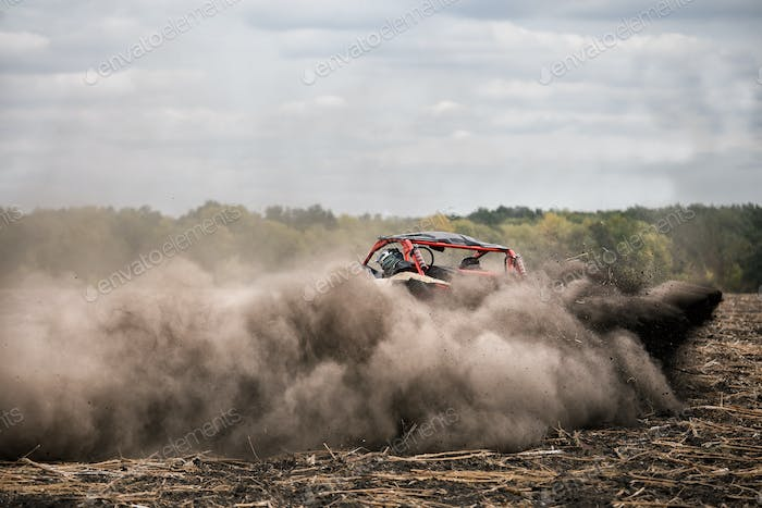 Quad bike with driver in cab rushes through field in dust