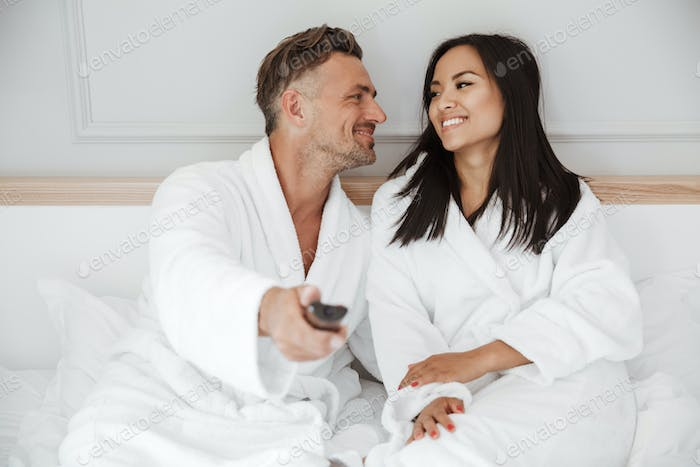 Lovely couple 30s caucasian man and asian woman wearing white ho