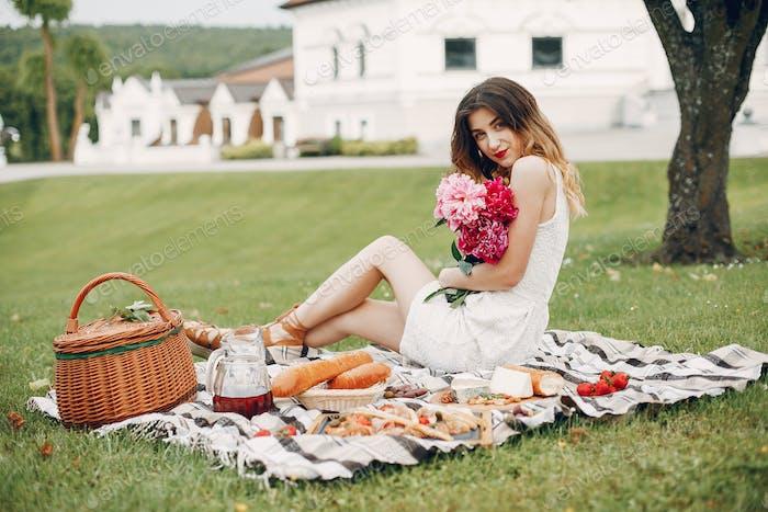 Elegant and stylish girl in a summer garden