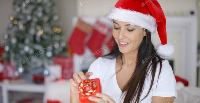Smiling woman unwrapping her Christmas gift