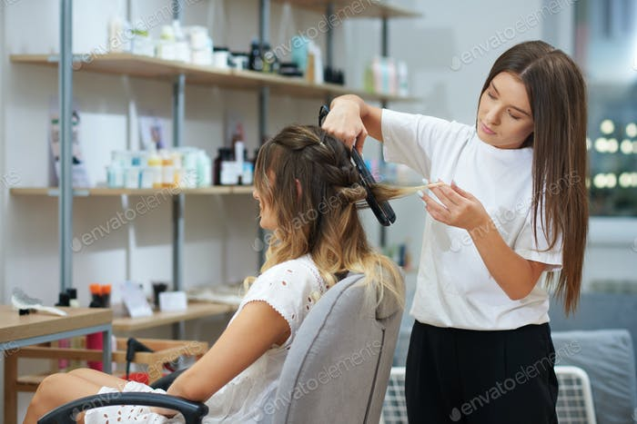Client relaxing while getting hairstyling in beauty salon