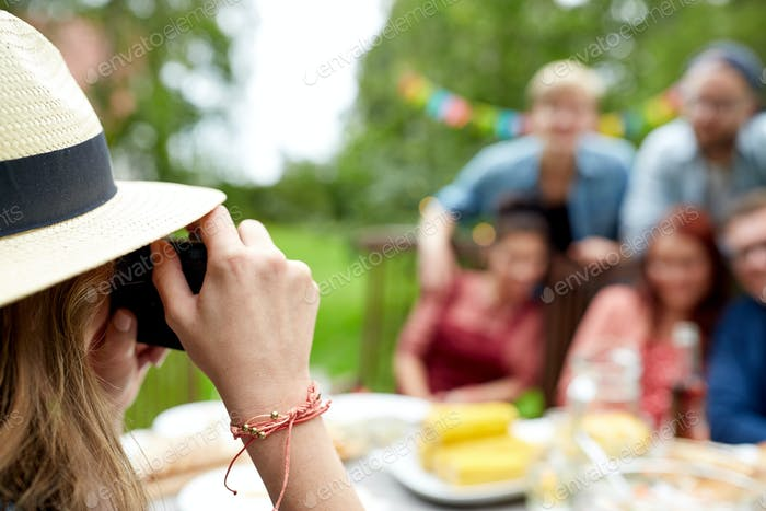 woman photographing friends at summer garden party
