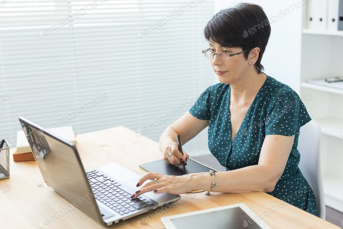 Photography and graphic art concept - Graphic designer using her tablet in a bright office
