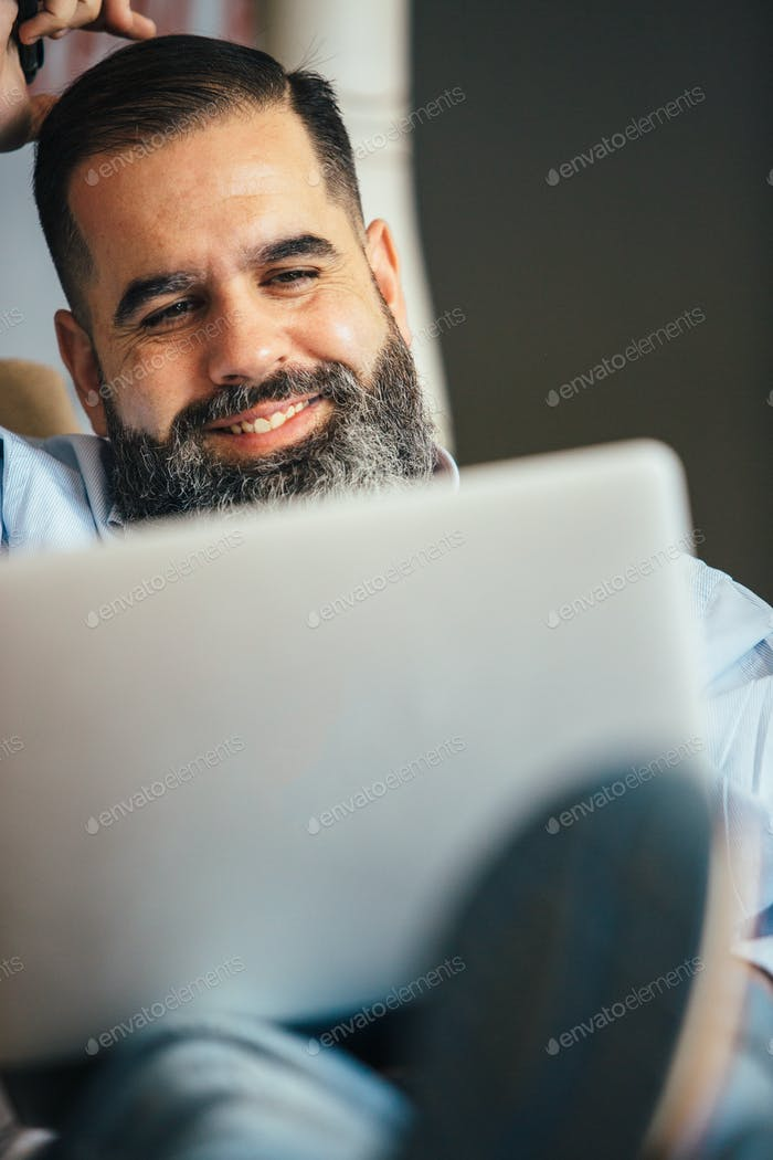Smiling bearded man with laptop