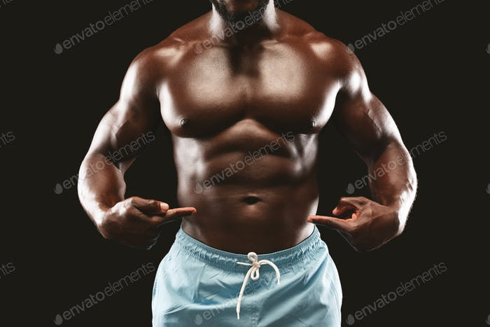Black muscular bodybuilder pointing at his six packs