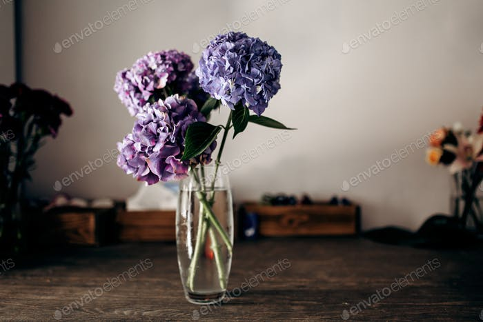 There is a vase with blue and lilac hydrangea on the wooden tabl