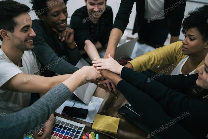 Equipo de trabajo mostrando la unidad con la mano unida.