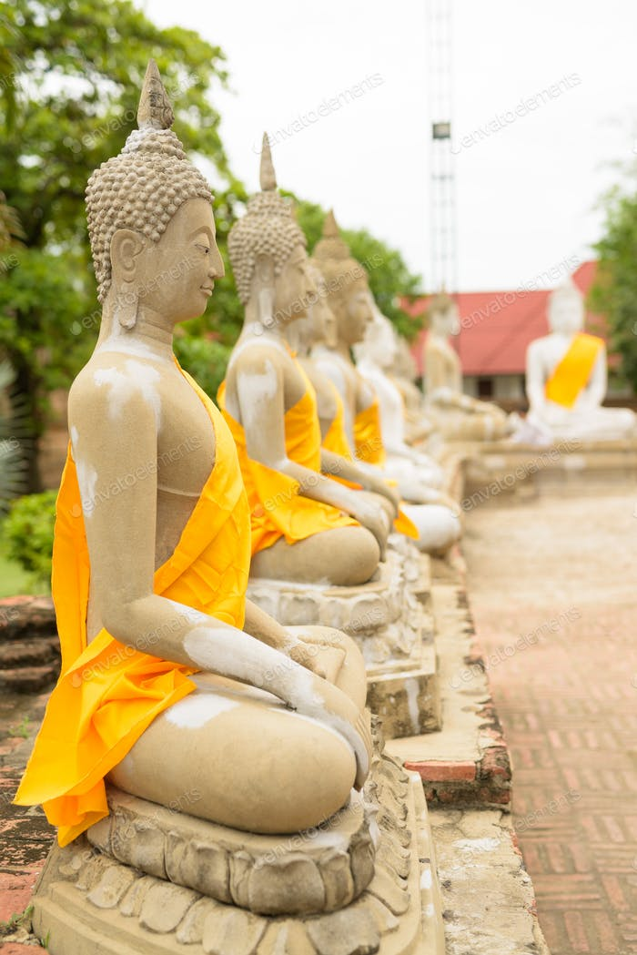 Sculpture of Buddha in rows with yellow robe wrapped around each
