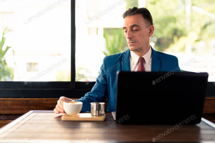 Mature handsome Italian businessman relaxing at the coffee shop